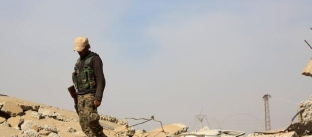 A US-backed fighter treads on rubble left by conflict inside Syria / nytimes.com