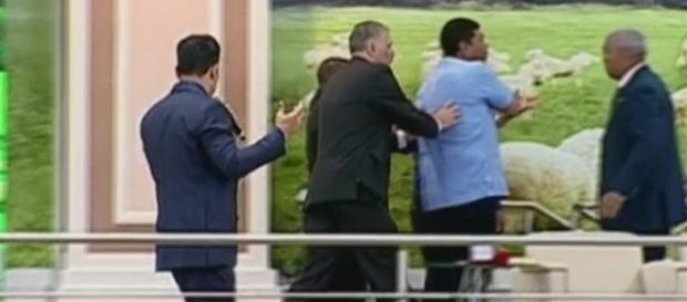 Na imagem o momento em que o pastor sai do palco já tampando com a mão um dos lugares do ferimento.