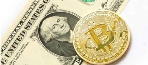 Bitcoin coin and a US dollar [Image Credits:Tombark/Pixabay]