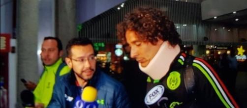 El guardameta mexicano Guillermo Ochoa salió con collarín en el aeropuerto