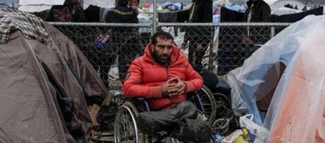 A man sitting on a wheelchair in a Greek refugee camp.