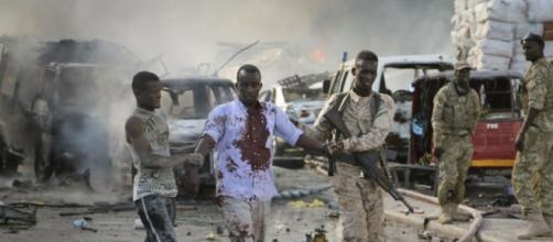A Somali soldier and local both help a civilian who was wounded in the blast in the capital.