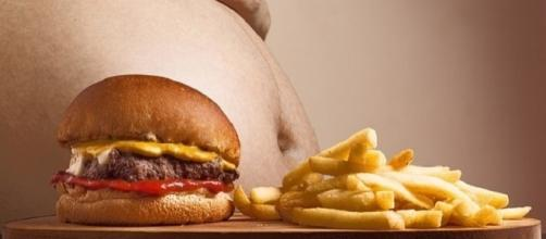 Obese person seated next to food [Image Credits: Joenomias/Pixabay]