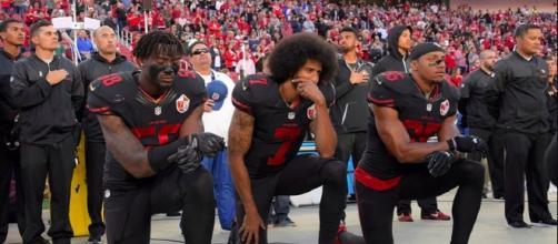 San Francisco 49ers' Eli Harold, Colin Kaepernick and Eric Reid kneel during the national anthem. [Image via Marie Louise Meewah/Flickr]