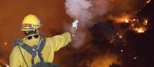 A firefighter shoots a flare to set back burn while battling the California wildfires.[image credit;Andrea Booher/wikimedia commons]