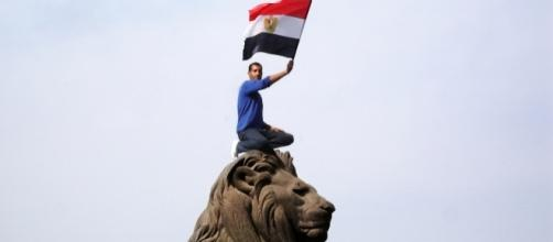 An Egyptian protestor waves the Egyptian flag. Photo by Kodak Agfa via Wikipedia Commons.