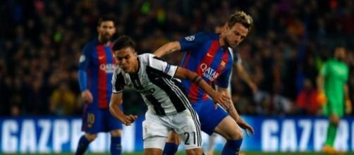 Paulo Dybala, 24 anni, contende il pallone a Ivan Rakitic, 29 anni, sotto lo sguardo di Leo Messi