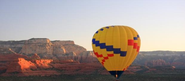 A hot air balloon glides over scenic Sedona in Arizona.[Image Credit;Thales/Flickr.com]