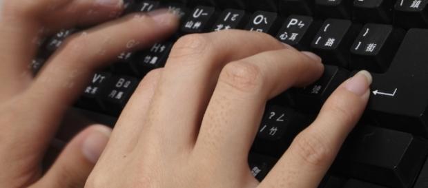 Woman typing /[Image via Adikos via Flickr]
