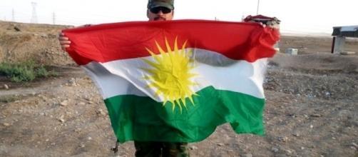 Peshmerga fighter holding flag. [Image Credit: Kurdishstruggle/Flickr]