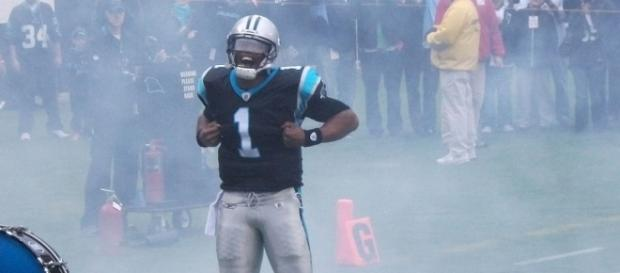 Cam Newton performing his Superman touchdown celebration [Image via Pantherfan11/Wikimedia Commons]