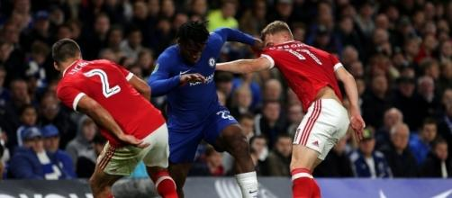 Chelsea striker, Michy Batshuayi is sandwiched by Nottingham Forest players in a past event. [Image Credit: Dan Westwell/Flickr]