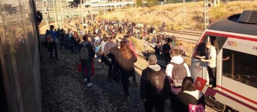 Usuarios de Cercanías este lunes caminando por las vías de Atocha tras estar encerrados mas de 25 minutos por una incidencia.