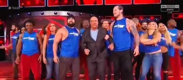 'SmackDown Live' superstars bring 'Raw' General Manager Kurt Angle to the ring after they invaded his show. [Image via WWE/YouTube]