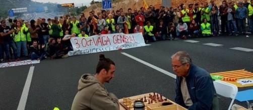 Trabajadores catalanes cortan una carretera mientras juegan al ajedrez. Fotografía de @PTalamanca