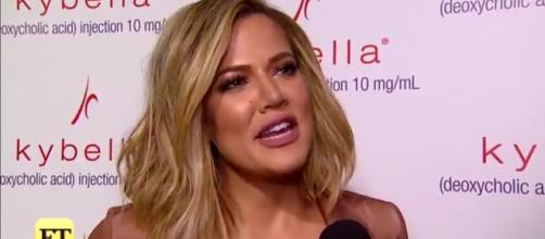 Khloe Kardashian tries to hide her pregnancy bump. [Image credit: Entertainment Tonight/Youtube screenshot]