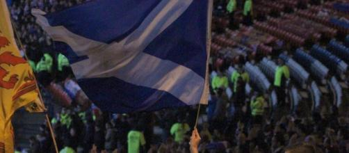 A section of Scotland fans waving their flag in a past match. [IMAGE/ Flickr credit: RossMacDonald]