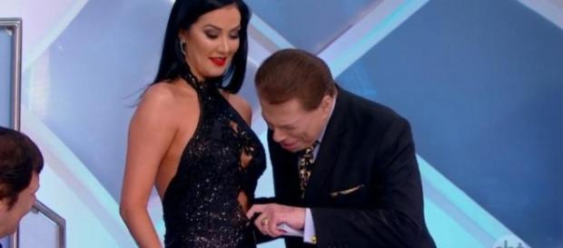 Silvio Santo olha espia por entre fresta do vestido de Helen Ganzarolli