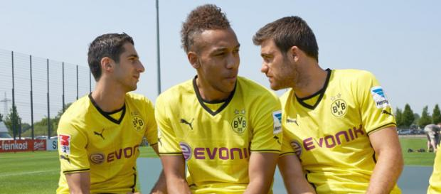 Borussia Dortmund striker, Pierre-Emerick Aubameyang (Center) sandwiched by his teammate on a bench. (Image via TotalFootball/Flickr)