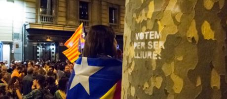 "Women dressed in the Catalan independence flag stands next to a spray painted tree that reads in Catalan ""We vote for being free"""