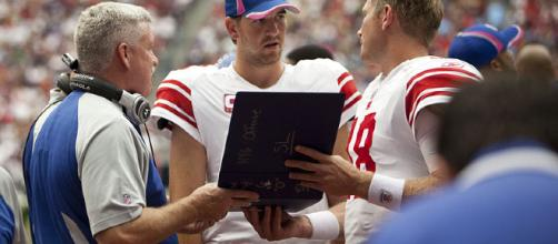 Eli Manning discussing the playbook [image credit: AJ Guel/ Wikimedia Commons]