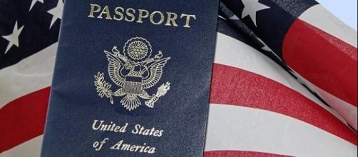 U.S. passport with American flag. (Image via 27707/Pixabay)