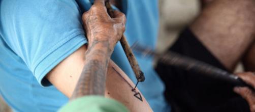 Whang-Od tatuando con herramientas tradicionales