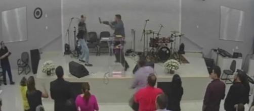 Momento em que o homem sobe no púlpito e ameaça o pastor. (Foto: reprodução vídeo)
