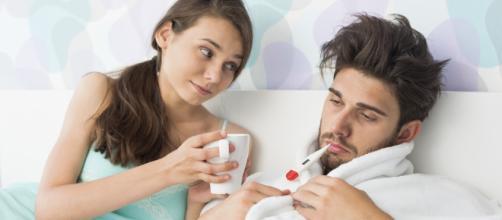 Un uomo a letto ammalato curato dalla compagna