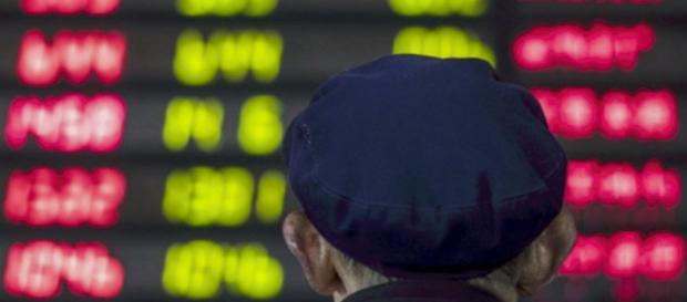 Un inversor observa una placa electrónica que muestra información bursátil en una casa de bolsa en Shanghai el 16 de marzo de 2017