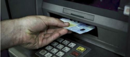 Un hombre retira efectivo de un cajero automático en Atenas el 19 de julio de 2016.