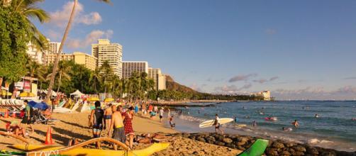 People on Waikiki Beach, Honolulu (Image credit – Cristo Vlahos, Wikimedia Commons)