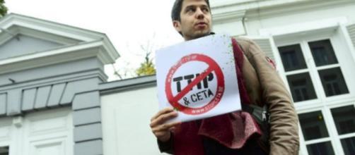 """Un demostrador sostiene un cartel que dice """"Stop TTIP - Stop CETA"""""""