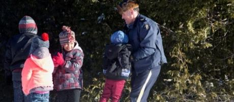 RCMP assisting family from Sudan crossing US - Canada Border from Champlain NY (credit Reuters Christine Muschi)