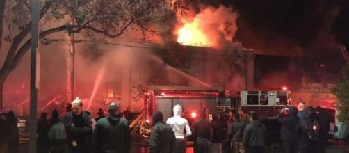Survivors of the Dec. 2 Ghost Ship fire in Oakland watch from street as firefighters battle blaze that killed 36. (Photo: sfgate.com)