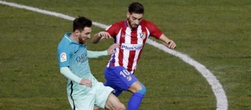 Messi y Carrasco peleando por un balón