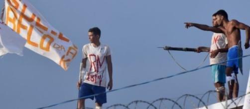 Reeducandos portando arma branca e bandeiras com palavras de ordem