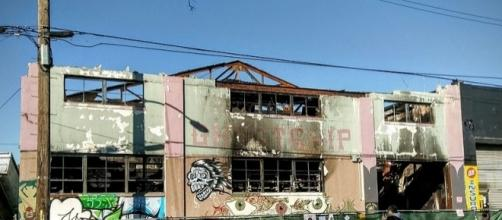 A mourner views tributes left at burned-out artists' live/work space in Oakland, Calif., where 36 died on Dec. 2 (Photo: Jim Heaphy/Wikimedia Commons)