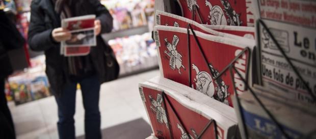 un lettore acquista l'ultimo numero della rivista satirica Charlie Hebdo