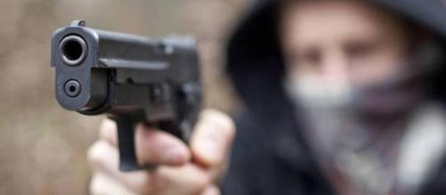 Un uomo compie una rapina armato di pistola, immagine di repertorio
