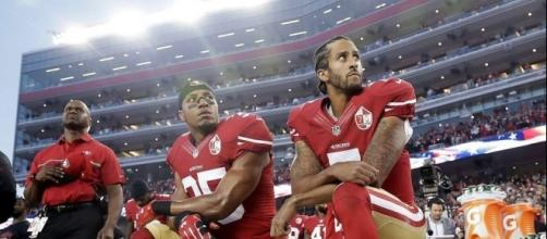 San Francisco 49ers' quarterback Colin Kaepernick (right) and safety Eric Reid kneel for the national anthem last year. (Photo: SFGate.com)