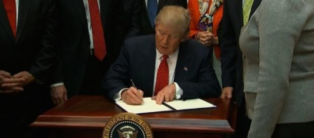 Donald Trump is signing the order. Photo via CNN.com.