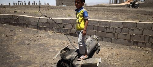 Un petit garçon joue sur un morceau d'obus qui a explosé près de son domicile - PHOTO: UNICEF/MOHAMED HAMOUD