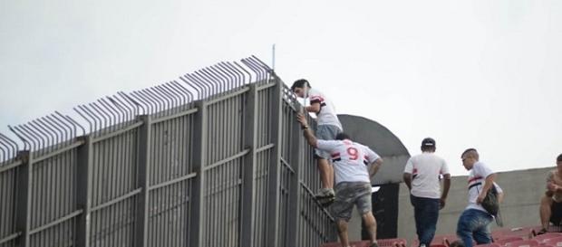 Na imagem torcedores tentando pular as grades que separam os setores da arquibancada do estádio. (Reprodução/Youtube/Arquivo pessoal).