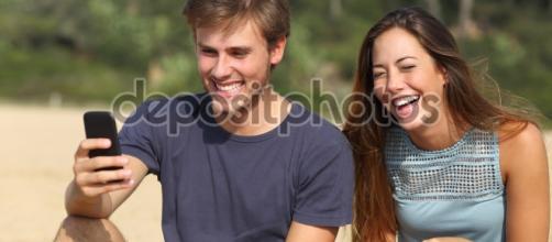 Gracioso hombre y mujer riendo mirando el teléfono inteligente ... - depositphotos.com