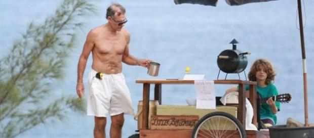 Ator Mario Gomes vende lanche na praia ao lado de seu filho.