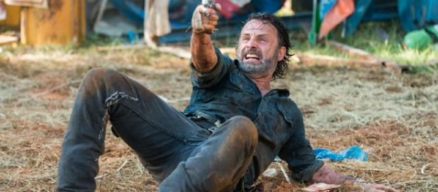 Rick Grimes atirando nos zumbis, após ter caído no chão