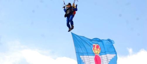 Paracaidista de la PAPEA desciende con la bandera del Ejército del Aire.