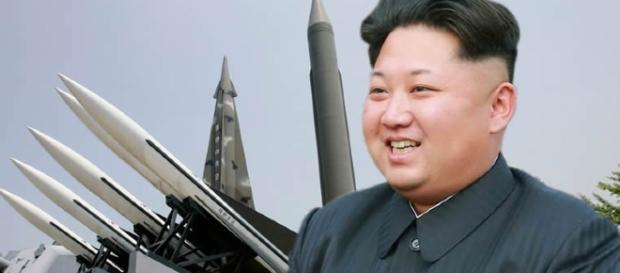 North Korea President Kim Jong-un smiling with a missiles visible in his background.