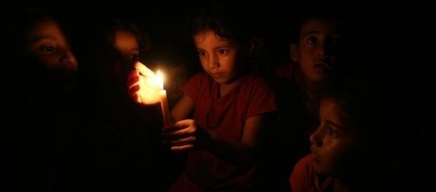 Niños palestinos se alumbran con una vela (cortesía ONU).